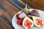 Lychee and figs on a wooden table — Stock Photo