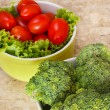 Fresh broccoli, cherry tomatoes, salad in bowls — Stock Photo