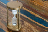 Hourglass on wooden table — Stok fotoğraf