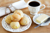 Brazilian snack pao de queijo (cheese bread) white plate butter  — Stock Photo