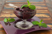 Acai pulp in glass with fresh mint on purple plate — Stock Photo