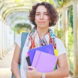 Young happy smiling woman (student, teacher) holding books — Stock Photo #51204437