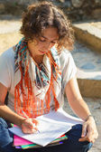 Young beautiful woman reading and writing in excercise book outside — Stock Photo