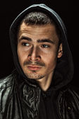 Brutal portrait of a young man in a hood — Stock Photo