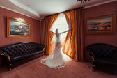 The bride standing on the window behind the curtains — Stock Photo