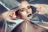 Woman with creative eye makeup peering cellophane — Stock Photo