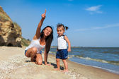 Girl with mother on the beach by the sea — Stock Photo