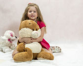 The lovely girl embraces a big soft toy hare — Stock Photo