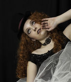 Beautiful young woman wearing black sequin top and white crinoline with hand up at her face — Stock Photo