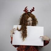 Beautiful young woman holding blank sign and wearing antlers — 图库照片