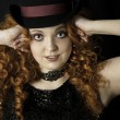 Beautiful young woman with long, curly, red hair wearing top hat — Stock Photo #43438103