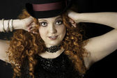 Beautiful young woman with long, curly, red hair wearing top hat — Stock Photo