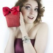 Cute young woman holding red, glittering gift box with bow — Stock Photo #44386025