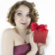 Cute young woman holding glittering, red gift box — Stock Photo #44386027
