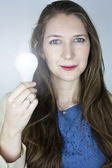 Woman holding lit light bulb — Stock Photo