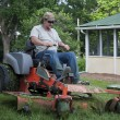 Landscaper on riding lawn mower — Stock Photo #48387835
