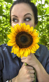 Woman holding sunflower to her face — Photo