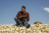 Young casual man working with touch pad at the beach — Foto Stock