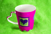 Colorful cup with background with colored fabric — Стоковое фото
