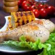 Stock Photo: Chicken thigh with boundary of corn cob and salad