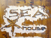 Wood carving with jellyfish and caption sea house — Zdjęcie stockowe