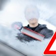Winter driving - woman scraping ice from a windshield — Stock Photo #39220669
