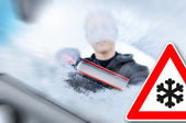 Winter driving - woman scraping ice from a windshield — Stock Photo