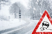 Winter driving - snowfall on a country road with warning sign — Stock Photo