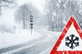 Winter driving - snowfall on a country road with warning sign — Foto Stock