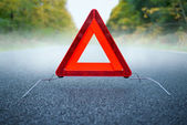 Caution fog - warning triangle on a foggy road — Stock Photo