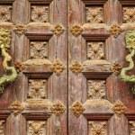 Old wooden doors with bronze door knockers — Stock Photo #38386407