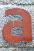 Letter A to rusty iron in granite wall — Stock Photo