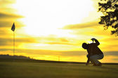 Golfer on green backlit sunset — Stock Photo