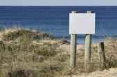 Wooden blank white billboard on sandy beach — Stockfoto