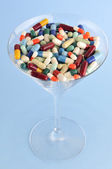 Colorful pills and tablets in cocktail glass — Stock Photo