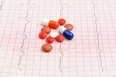 Electrocardiograma con píldoras y tabletas de arriba, — Foto de Stock