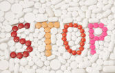 Pills and drugs forming word STOP in english text — Stockfoto