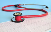 Red stethoscope and EKG paper — Photo