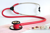 Red stethoscope and EKG paper — Stock Photo