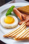 English Breakfast - sunny-side-up fried eggs, sausages, beans, bacon and toasts served with coffee — Stock Photo