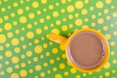 Coffee cup in green and yellow setting — Stock Photo