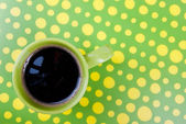 Coffee cup in yellow and green setting — Stock Photo