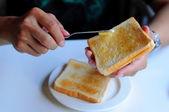 Sprida smör på toast — Stockfoto