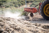 Tractor plowing or tilling an agricultural field — Stock Photo