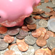 Stock Photo: Conceptual Piggy Bank on its Side on Loose Change