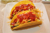 Two Tacos on a White Plate with Cheese and Sauce — Stok fotoğraf