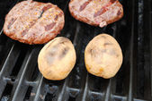 Grilling Whole Potatoes and Hamburgers — Stock Photo