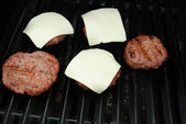 Melting Cheese on Meaty Burgers on a Grill — Stock Photo
