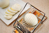 Slicing a Boiled Egg with a Plate in the Background — Stockfoto