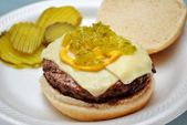 Cheeseburger with relish, pickles and mustard — Stock Photo
